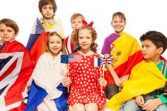 Children with flags wrapped in different banners - stock photo
