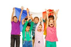 Group of seven kids smiling and waving French flag - stock photo