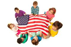 Children in a circle around the flag of America Stock Photos