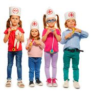 Kids with medical caps and toy doctor tools - stock photo