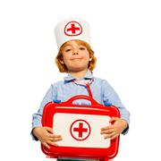 Young boy with medical cap and toy first-aid kit - stock photo