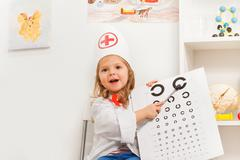 Girl playing doctor with oculist sign and pointer - stock photo
