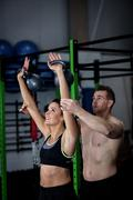 Trainer assisting a woman while exercising with kettlebell Stock Photos