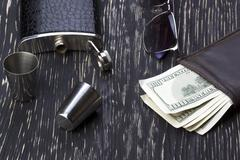Metal flask trimmed leather, metallic  shot glasses, wallet and sunglasses - stock photo