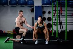 Trainer instructing a woman while lifting barbell Stock Photos