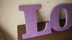 Purple inscription Love is on the table at home Stock Footage
