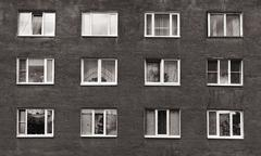 black and white windows of the old multistory building - stock photo
