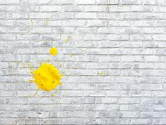 White brick wall stained spots of paint of yellow colors Stock Photos