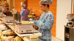 Attractive saleswoman weighing cheese in a large supermarket Stock Footage
