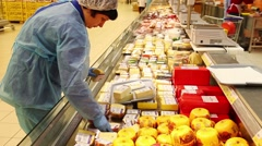 Saleswoman arranges cheese on a showcase in a large supermarket. - stock footage