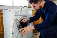 Handyman repairing a washing machine Stock Photos