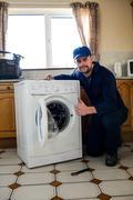 Portrait of handyman repairing a washing machine Stock Photos