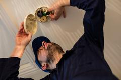 Handyman installing smoke detector Stock Photos