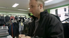 Man shopping for clothes and speaks to cashier Stock Footage