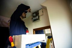 Electrician repairing a switch board Stock Photos