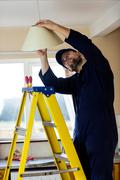 Electrician repairing a ceiling lamp Stock Photos