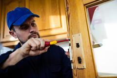 Man fixing the door handle with screwdriver Stock Photos