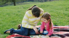 Mum reads a fairy tale daughter in the park - stock footage