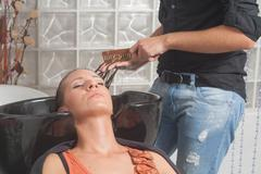 Close up of hair stylist washing hair. - stock photo
