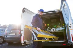 Portrait of handyman loading a ladder Stock Photos