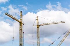 Two construction cranes on  blue sky background - stock photo