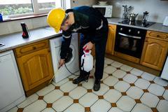 Pest control man spraying pesticide Stock Photos