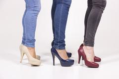 close up three girls in fancy high heel shoes, red, blue and white. - stock photo