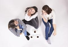 Elevated view, shot from above, three girls chatting. White background - stock photo