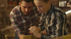 Father and son are woodworking in a garage at home - stock footage