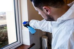 Man doing pest control in kitchen Stock Photos