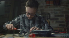 Young boy is soldering a circuit board in a garage at home Stock Footage