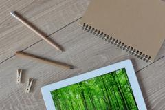 Natural and ecological life. Green forest in your tablet. - stock photo