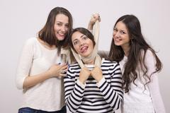 Two friends choking third girl with scarf. Stock Photos
