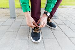 Close up of male hands tying shoe laces on street Stock Photos