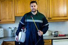Portrait of pest control man spraying pesticide Stock Photos