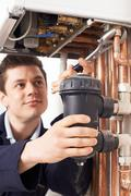 Male Plumber Working On Central Heating Boiler Stock Photos