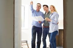 Couple Meeting With Architect Or Builder In Rennovated Property - stock photo