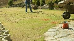 Woman farmer raking mowed grass in garden 4K - stock footage
