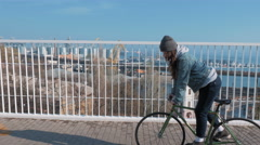 Young attractive girl riding fixed gear bike on the bridge Stock Footage