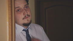 Drunk man comes home drunk and breathing heavily dropping tie. Close up. - stock footage