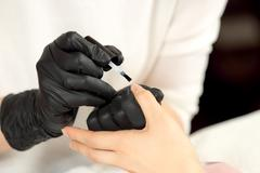 Manicurist cover colorless varnish nails client Stock Photos