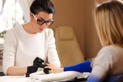 Manicurist works and paints nails client Stock Photos