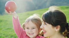 Girl 3 years holding an apple in hand, hugging her mother. Hold out apple to the Stock Footage
