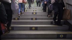 Slow motion of commuters on stairs with arrows of direction, Tokyo - stock footage