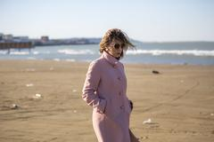 depressed young woman near the sea in a windy day - stock photo