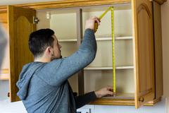 Handyman measuring a cabinet with measuring tape Stock Photos