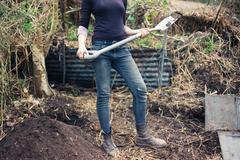 Young woman in garden with spade Stock Photos