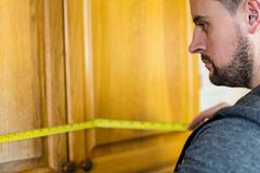 Handyman measuring a furniture with measuring tape Stock Photos