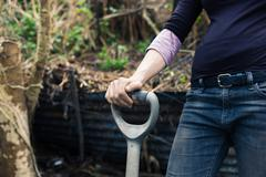 Young woman resting hand on spade Stock Photos
