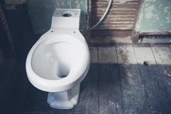 New toilet in derelict bathroom - stock photo